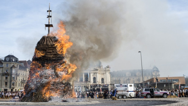 Reiter galoppieren um brennenden Scheiterhaufen am Zürcher Sechseläuten
