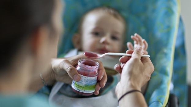 Ein Mann füttert ein Baby mit Brei.