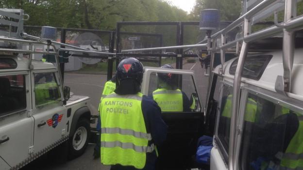 Drei Polizisten zwischen Polizei-Einsatzwagen.