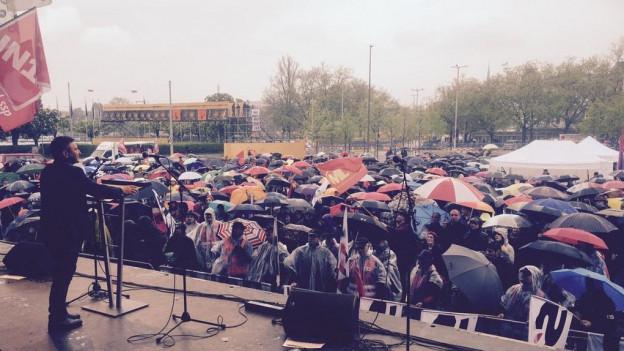 Blick von der Rednerbühne auf ein Meer von Regenschirmen am Sechseläutenplatz.