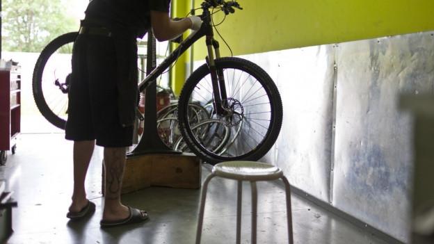 Mann repariert Velo in Werkstatt
