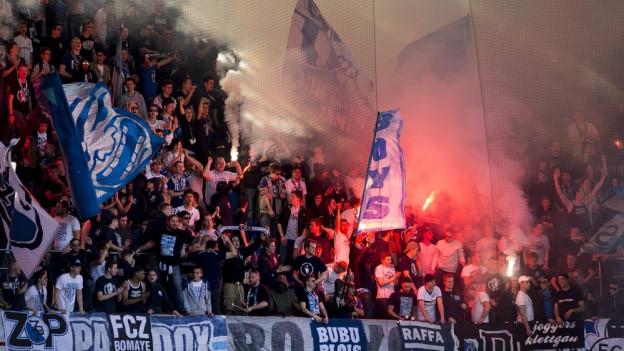 Fussballfans in einem Stadion zünden Fackeln.