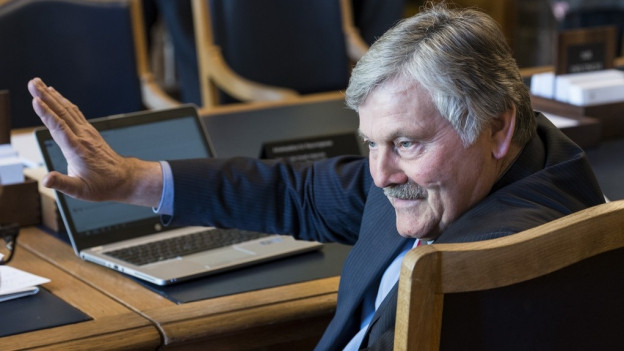 Hans Fehr auf seinem Sitz im Nationalratssaal hebt abwehrend die Hand vor sich.