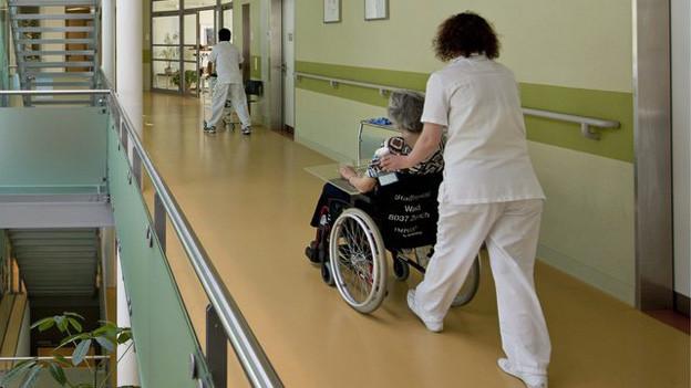 Eine Spitalmitarbeiterin schiebt eine betagte Patientin im Rollstuhl durch die Gänge des Waidspitals.