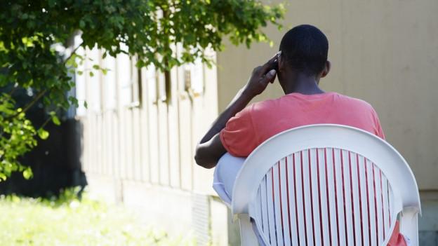 Ein schwarzer Mann sitzt auf einem weissen Gartenstuhl.