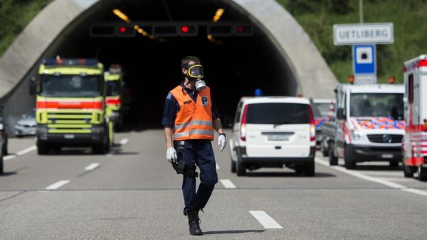 Ein Polizist mit Gasmaske steht vor dem Portal des Uetlibergtunnels, das mit Einsatzfahrzeugen verstellt ist.