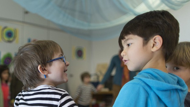Kinder spielen im Kreis in einem Kindergarten.
