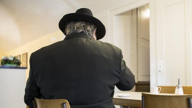 Ein Mann mit Hut sitzt auf einem Stuhl und wartet auf eine Beratung