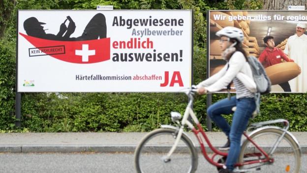 Eine Velofahrerin vor einem Abstimmungsplakat der SVP.