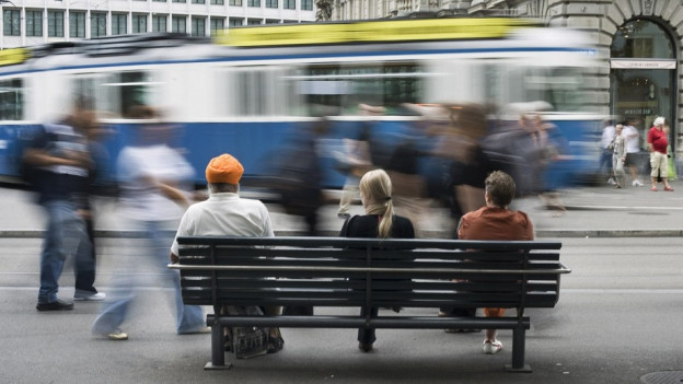 Paradeplatz Zürich: Passagiere sitzen auf einer Bank und schauen eine Tram zu, das in die Haltestelle einfährt