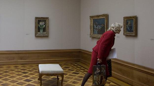 Eine Frau schaut sich ein Bild an.