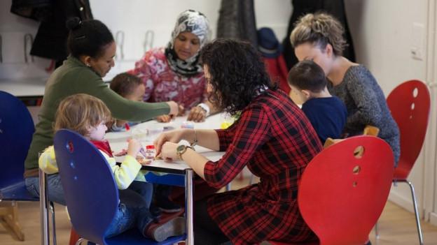 Frauen, Kinder, Betreuerinnen des Projekts Zeppeliin sitzen zusammen um einen Tisch.
