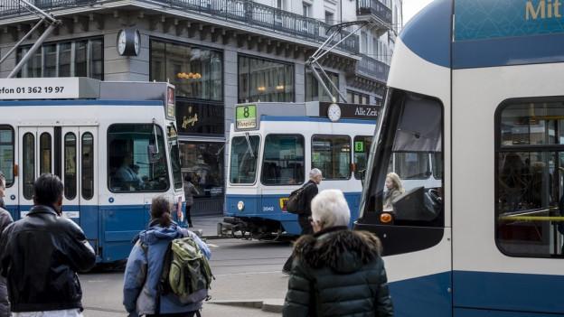 Paradeplatz Zürich mit einfahrenden und haltenden Trams und ein paar wartenden Passagieren