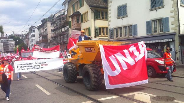 Ein Kipper mit einer Unia-Fahne, dahinter ein Demonstrationszug