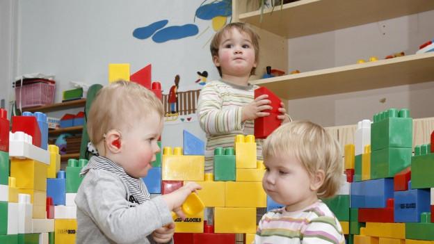 Drei Kinder spielen mit Lego