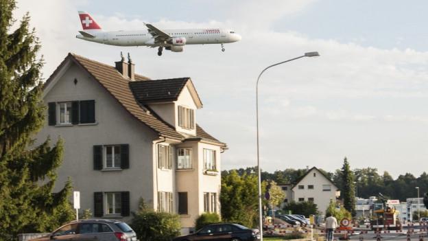 Flugzeug fliegt über einem Hausdach an