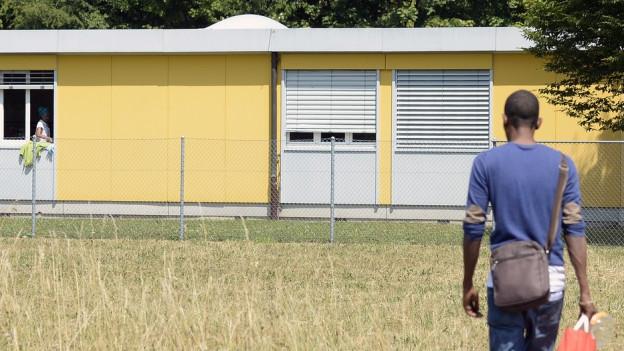 Mann geht auf gelbes Gebäude zu