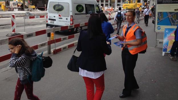 Eine VBZ-Mitarbeiterin verteilt am Bellevue Infoflyer.