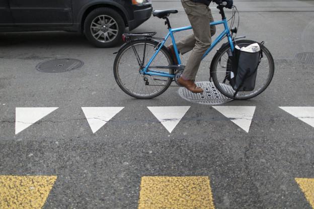 Ein Velofahrer im städtischen Autoverkehr