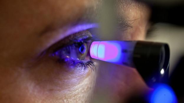 Eine Frau, dessen Auge untersucht wird.