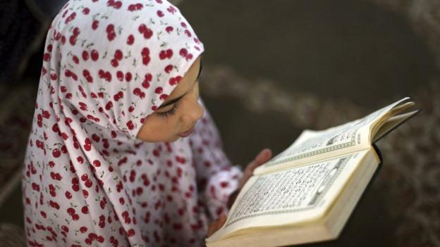 Ein Mädchen mit Schleier liest den Koran