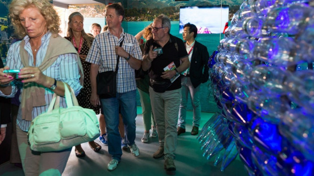 Menschen vor blau-grünem Hintergrund, rechts blaue Flaschen