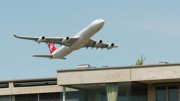 Ein Flugzeug startet über Siedlungsgebiet.