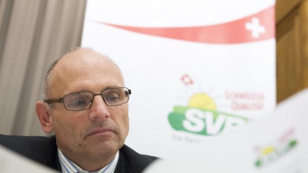 Ein Mann mit Halbglatze liest in einer Zeitung, dahinter das Logo der SVP.