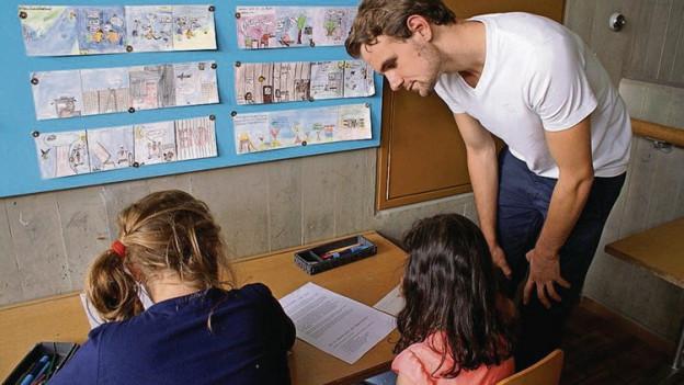 Ein Zivildienstleistender hilft zwei Mädchen bei den Schulaufgaben.