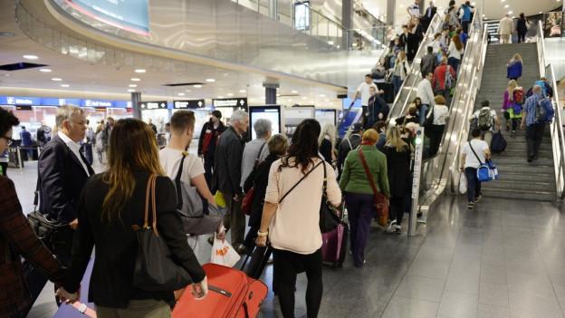 Menschenschlange vor den Rolltreppen im Flughafen Zürich