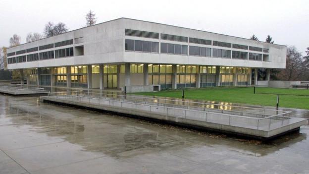 Der Betonklotz des Gymnasiums Freudenberg in Zürich, aufgenommen an einem trüben Regentag.