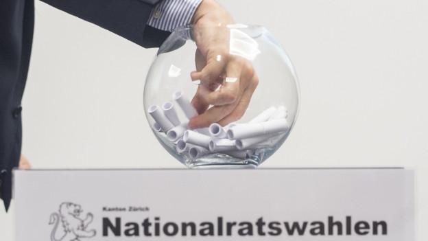 Eine Hand greift in ein grosses Glas mit Papierrollen