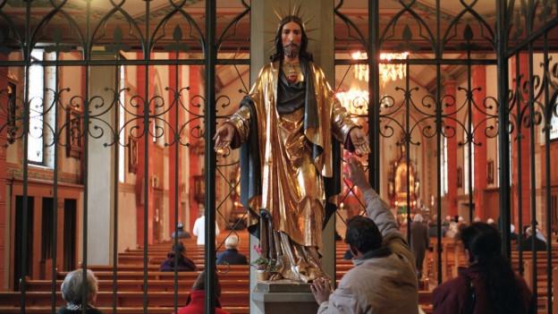 Besucher der roemisch-katholischen Kirche St. Peter und Paul in Zuerich betrachten eine Jesus-Statue, waehrend vorne ein Abendgottesdienst gefeiert wird