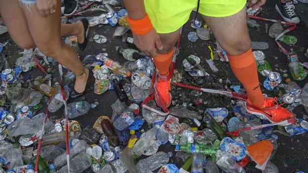 Zwei Menschen gehen durch eine mit Petflaschen bedeckte Strasse