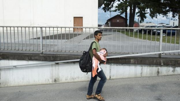 Ein Mann mit Kleinkind in den Armen geht auf der Strasse.