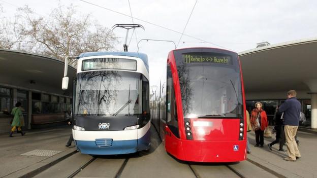Ein blaues und ein rotes Tram an einer Haltestelle.