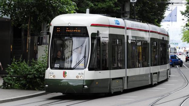 Ein grünes Tram fährt auf Zürcher Schienen