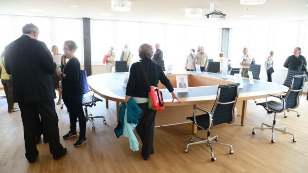 Stadtpräsident Michael Künzle neben dem Sitzungstisch des Stadtrates im Gespräch mit einer Besucherin