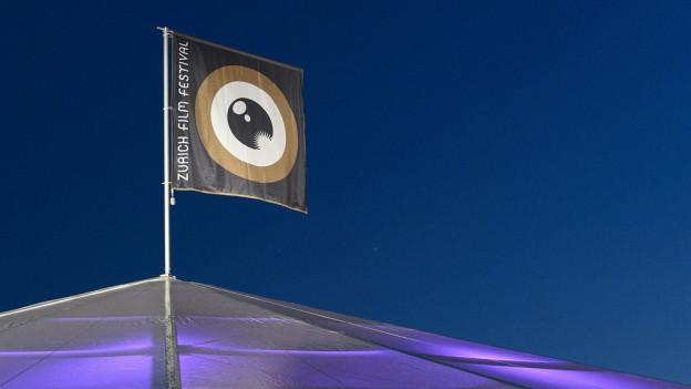 Das Fähnchen des Zurich Filmfestivals weht auf einem Dach.