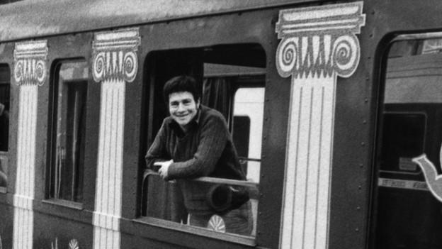 Ein junger Mann schaut aus einem Eisenbahnwagen. Schwarz-weiss Foto.