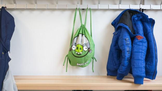 Eine Garderobe, am Haken hängt ein grüner Schulsack.