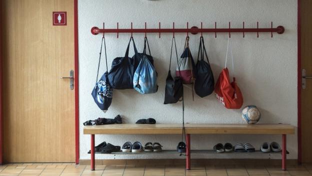 Eine Garderobe in einem Schulhaus, diverse Turnsäcke hängen an Haken.