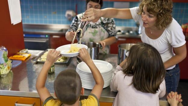 Eine Betreuerin in einem Zürcher Hort schöpft einem Kind Spaghetti.