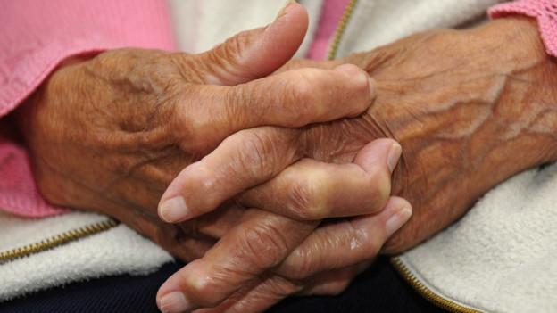 Gefaltete Hände einer hochbetagten Frau