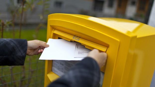 Ein Briefkasten, in den ein Wahlcouvert geworfen wird.