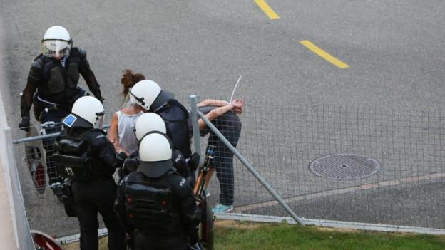 Polizisten kontrollieren eine Aktivistin beim Binz-Areal.