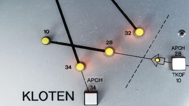 Die Pisten des Flughafen Zürich, eingezeichnet auf einer Metallplatte, daneben Lichter.