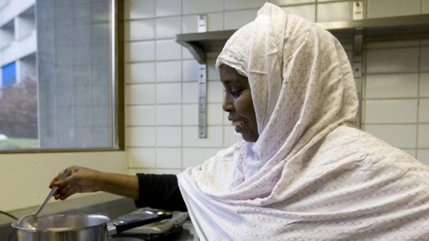 Eine Flüchtlingsfrau kocht eine Mahlzeit