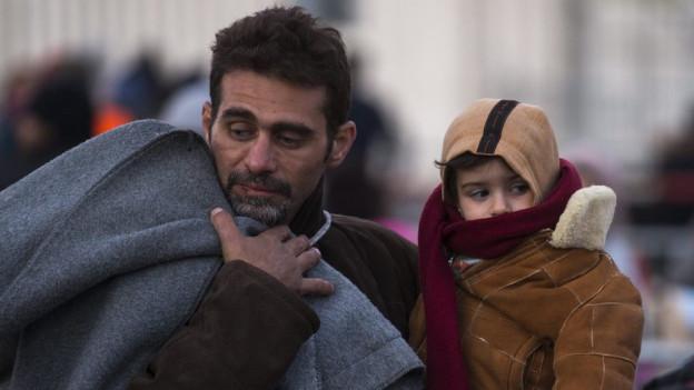 Flüchtling mit einem Kind auf dem Arm und einer Wolldecke über der anderen Schulter