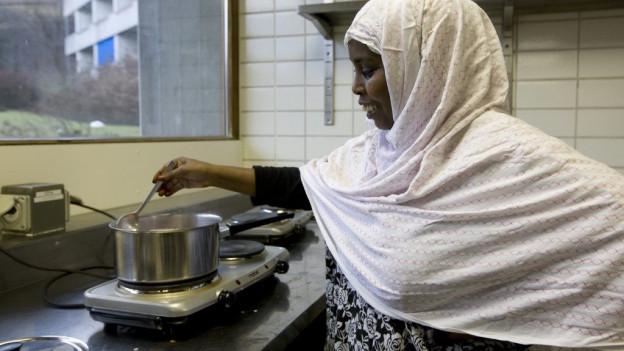 Eine Asylsuchende kocht.